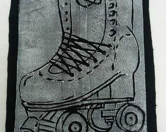 Get your skates on print- roller skate hand cut lino printed patch, white on black.