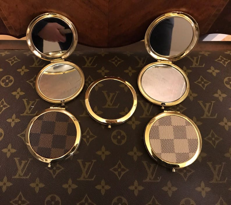 e833e50c42309 Compact double sided mirror hand covered with canvas from an authentic LV  monogram or Damier canvas. Also available in Gucci
