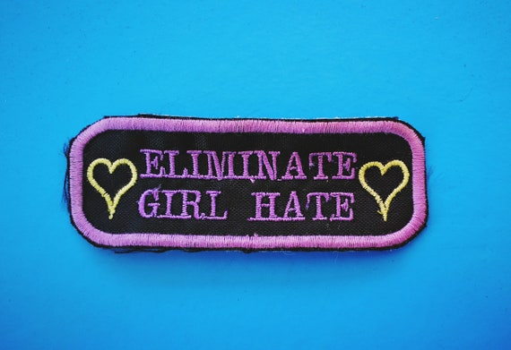 """Feminist patch embroidered on thread."""" Eliminate Girl Hate"""" Colors Lavender and Lime. 4x10 cm approximately"""