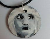 Necklace with hand-painted wooden pendant, the subject is the portrait of a black and white woman