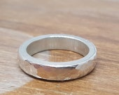 Sturdy hammer stroke incorporated into a heavy silver ring bulbous shiny and matted personalized possibly with custom engraving