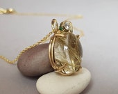 Unique heavy 14kt yellow gold pendant with diamond, rutiel quartz and mini emerald. Golden needles in the main stone particularly beautiful with necklace