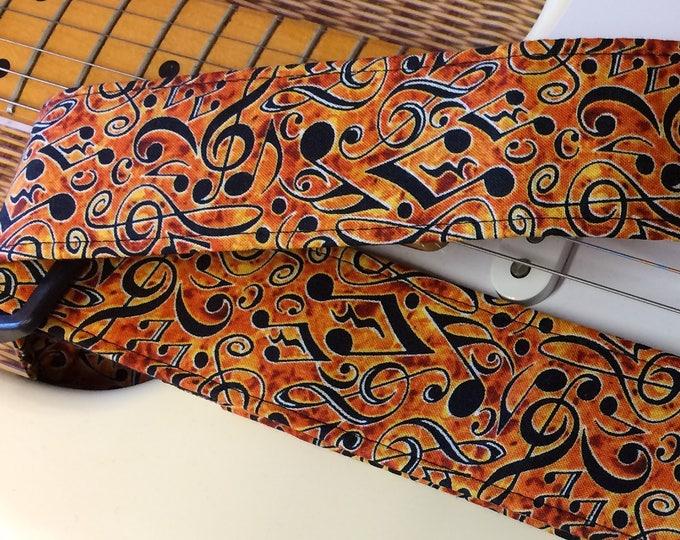 Music guitar strap // black musical symbols on an orange/yellow/bronze background // guitar teacher gift // music lover gift
