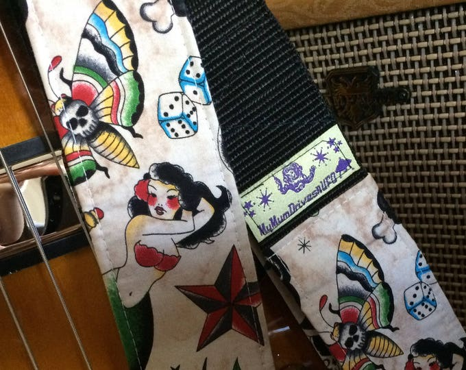 Tattoo guitar strap // multi-coloured retro images on cream // mermaids, butterflies, stars, four-leaf clover, Route 66, swallows, dice etc