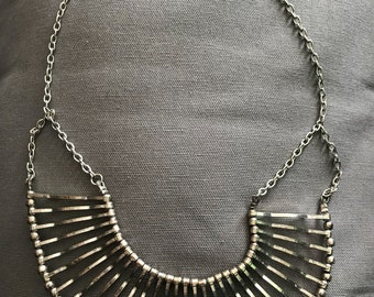 Metal bib necklace on adjustable chain.