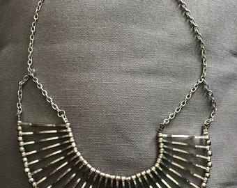 Metal bib necklace on adjustable chain.