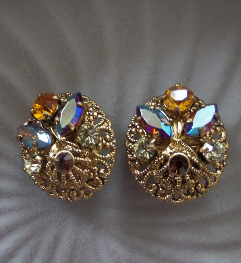 Vintage Round Circle Ornate Gold Tone Filigree Clip On Earrings with Dazzling Aurora Borealis Rhinestones Made In West Germany