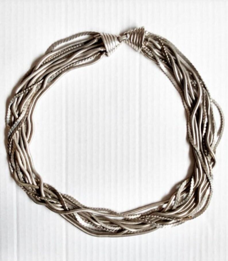 Multi strand silver tone metal necklace with unique clasp