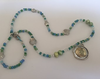 Hand crafted beaded necklace with starfish pendant in blues and greens