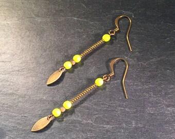 Long earrings with neon yellow beads.