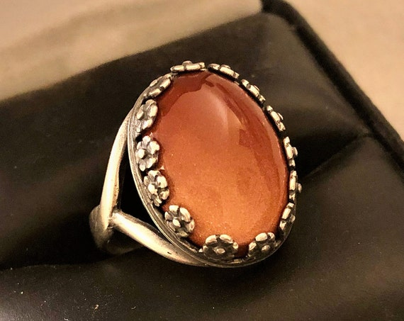 Goldstone adjustable ring encased in a Floral Silver Plated Setting.