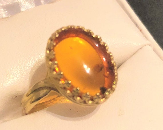 Amber adjustable Ring surrounded by a Brass Setting.