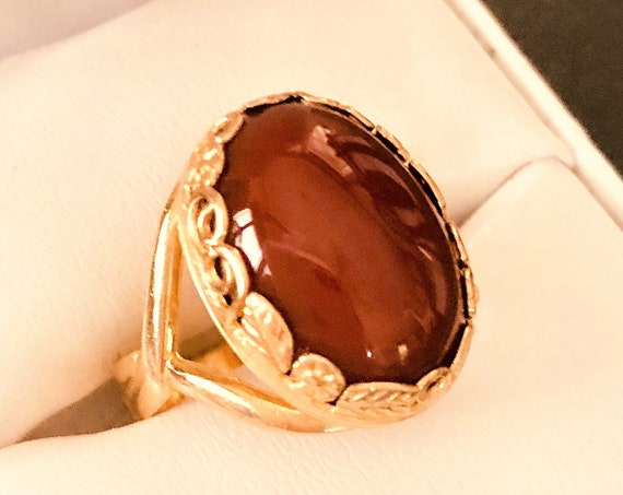 This Carnelian adjustable ring is set in a brass leaf and flower bezel setting.
