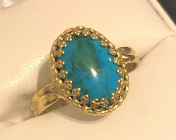 Turquoise adjustable Ring encased in a Brass Crown Setting.