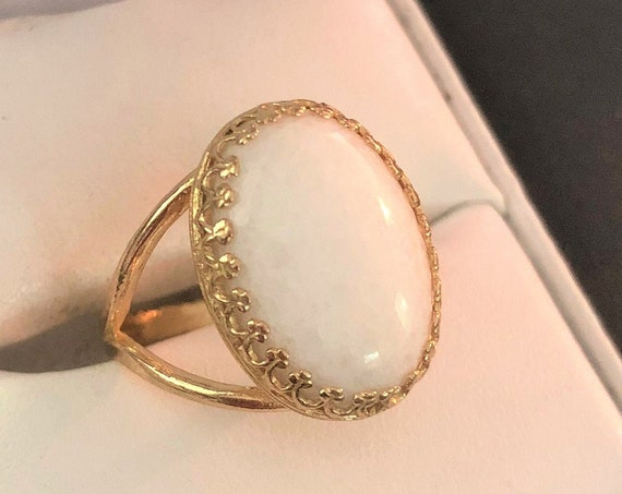 This White Quartz adjustable ring is surrounded by a brass crown bezel.