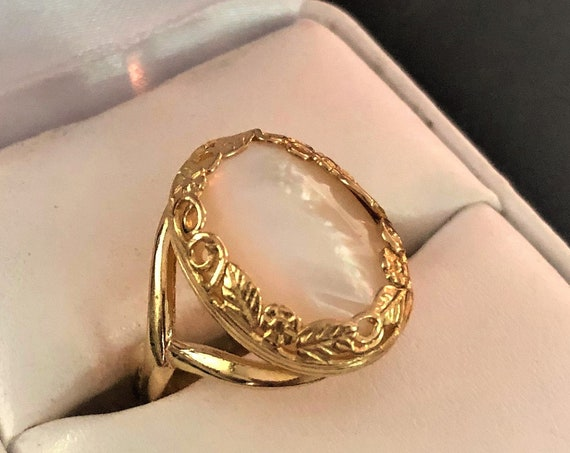 This adjustable Mother of Pearl ring is set in a brass flowers and leaves bezel.