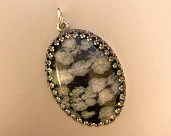 Snowflake Obsidian Cabochon encased in a Silver Plated Setting.