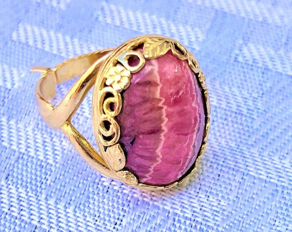 This Rhodochrosite Gemstone is nestled in a Brass Flower Bezel.