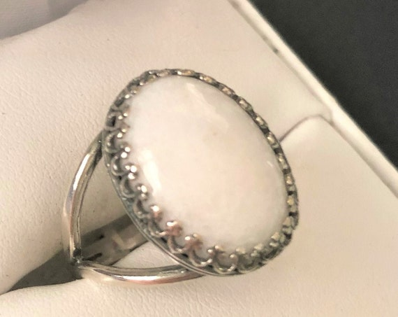 White Quartz adjustable ring is surrounded with a silver-plated crown bezel setting.