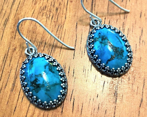 Turquoise earrings are set in a silver-plated crown bezel and dangle from sterling silver ear wires