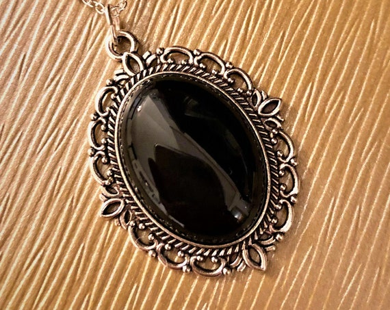 Black Onyx Cabochon Pendant surrounded in a Silver Plated Setting.