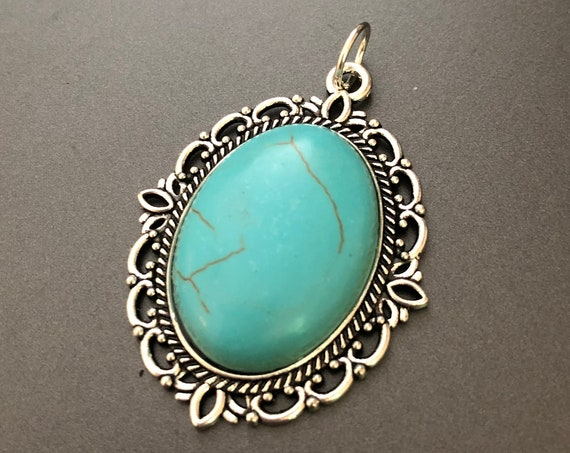 Natural Turquoise Cabochon surrounded by a Silver Plated Setting.