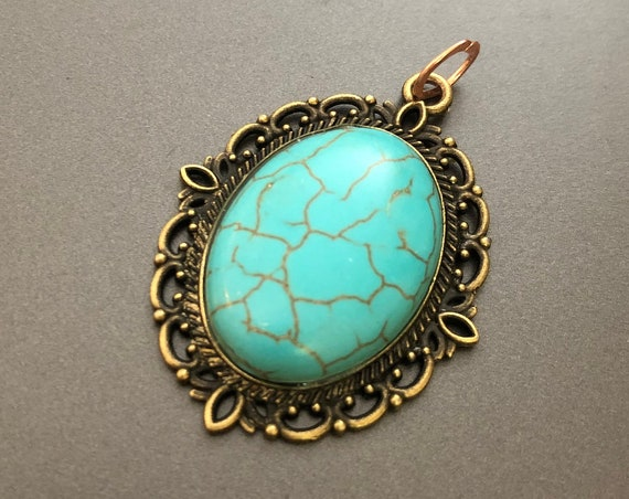 Natural Turquoise Cabochon surrounded by a Brass Setting.