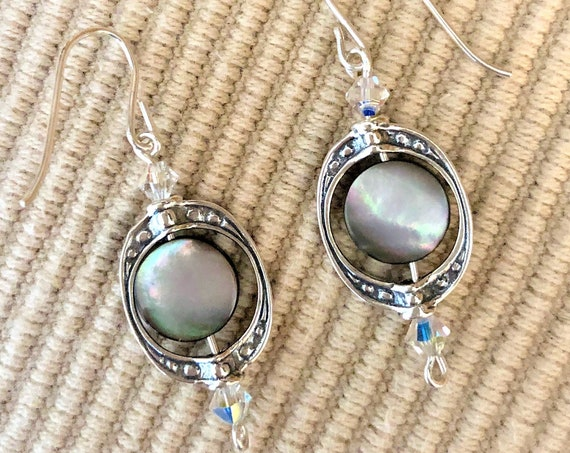 These earrings are surrounded by Swarovski Crystals on either end  of a fancy sterling silver bead frame encasing a shell bead.