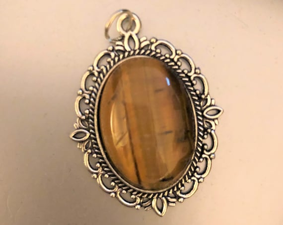 Tiger Eye Cabochon surrounded by a Silver Plated Setting.