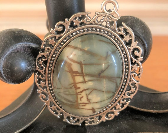 Picasso Jasper Cabochon resting in a Silver Plated setting.