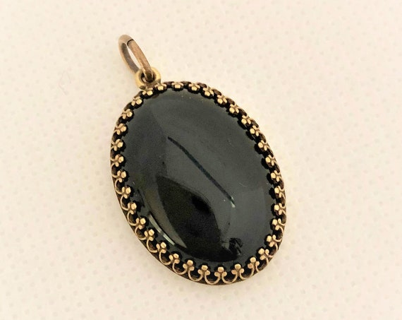 This Black Onyx Cabochon is set in a brass setting and includes an oxidized copper chain.