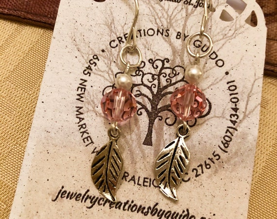 These earrings feature Swarovski Crystals and Swarovski Pearls with a lovely dangling Pewter Leaf.