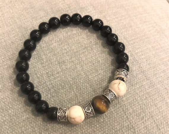 This mysterious and powerful Tiger Eye stretch bracelet is surrounded with Howlite, Black Jasper and Silver Plated Spacer Beads.