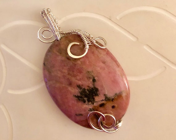 Rhodonite bead is encased in a Sterling Silver wire weave.