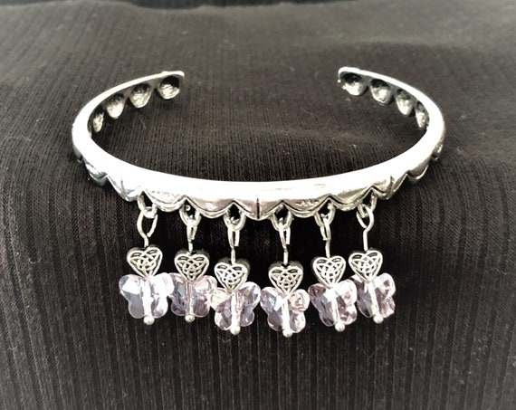 The Sparkling Pink Glass Butterflies and Silver Plated Heart Charms adorn this Bangle Bracelet