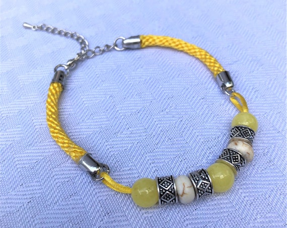 Satin Hand Braided Bracelet accented with Yellow Icy Jade, Howlite and Silver Plated Beads.