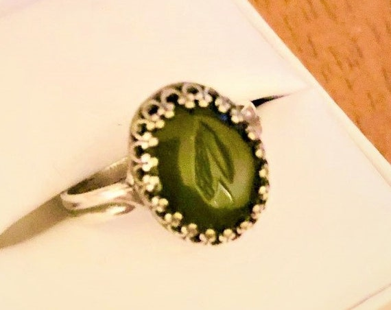 Adjustable Nephrite Jade rind is designed with a 10 x 14 mm gemstone in a silver plated crown setting.