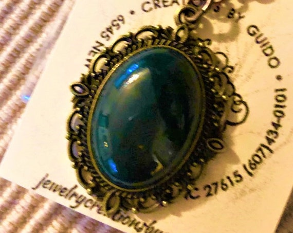 This Bloodstone pendant is accentuated by a brass setting and hangs from an antiqued copper chain.