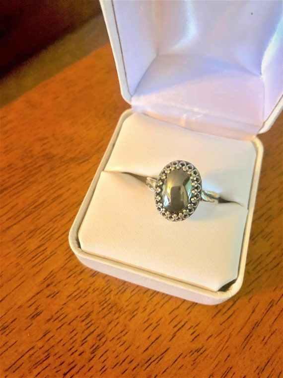 Hematite adjustable ring is encased in a silver-plated crown bezel.