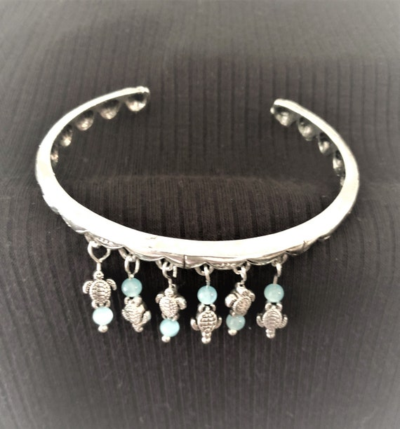 This Bangle Bracelet is adorned with Silver Plated Turtle Charms and Blue Opalite Beads.