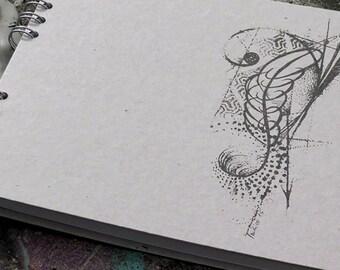 A tattooed spiral notebook