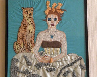 Woman and cheetah embroidery framed under glass.