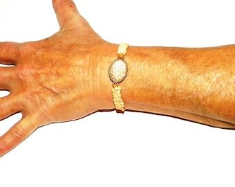 Orange macramé bracelet and rhinestone pearl.