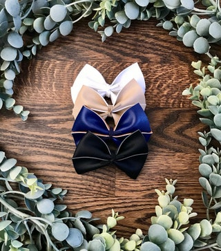 Large, smooth faux leather bow finished on a nylon headband or alligator clip. Available in white, nude, navy and black.