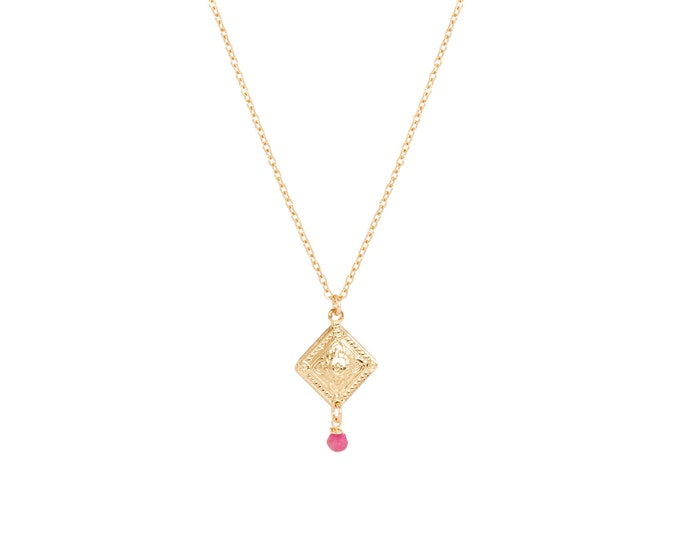 Gold necklace with an engraved pendant finished with a pink stone