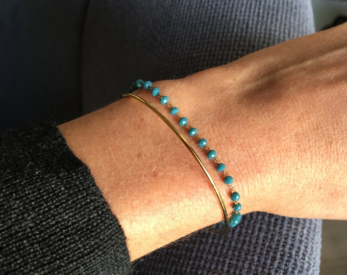 Golden jonc lined with a chain of blue tinted glass beads