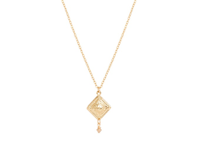 Gold necklace with an engraved pendant finished with a golden bead