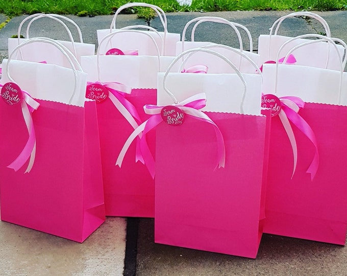 Hen party bachelorette favour bags team bride bright pink with matching ribbon and badge