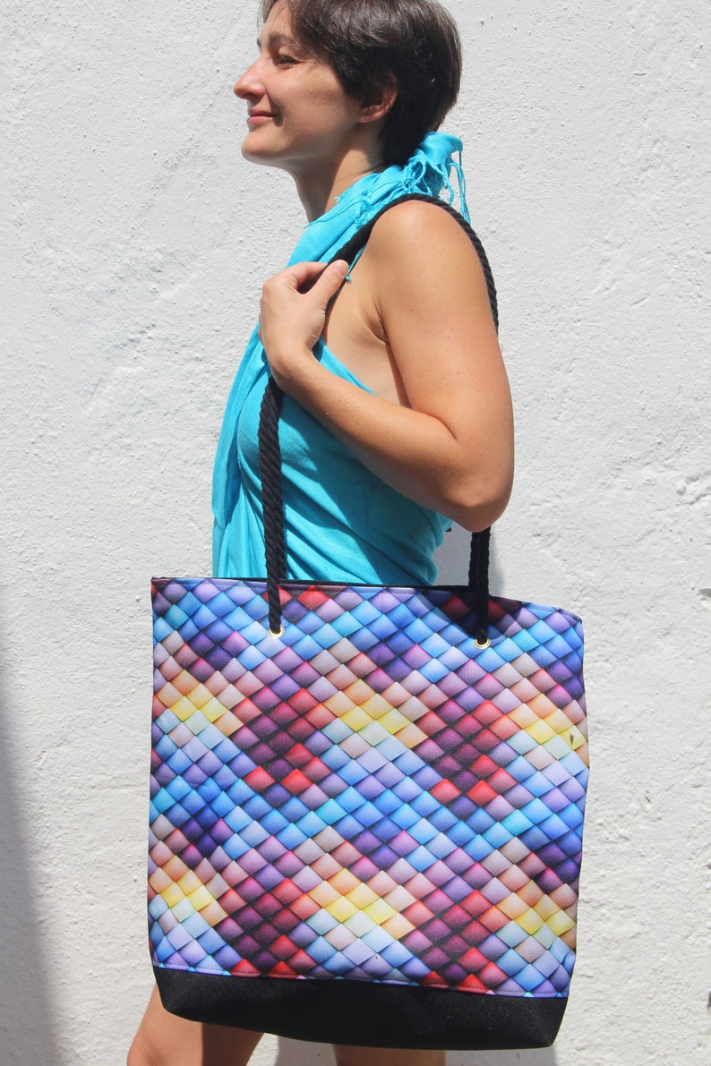 Colorful large waterproof beach bag with cord handles and internal zipped pocket.