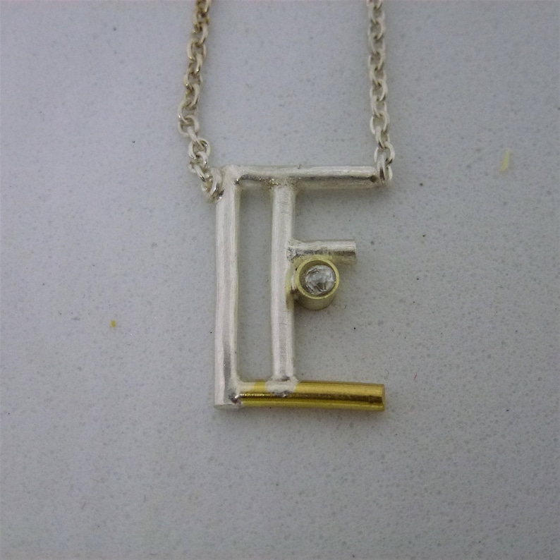 Letter pendant in RECYCLTEM silver and gold. image 0